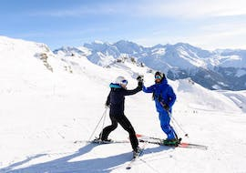 A skier and his ski instructor are high-fiving during the Private Ski Lessons for Adults of All Levels in Gstaad with Altitude Ski School Verbier & Gstaad.