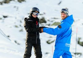 A skier and his ski instructor are laughing during the Private Snowboard Lessons for Adults in Verbier with Altitude Ski School Verbier & Gstaad.