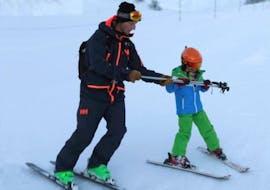 Un moniteur de ski montre à un enfant comment tenir les bâtons de ski correctement pendant son cours particulier de ski pour enfants - megève avec l'école de ski Skibex.