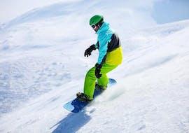 Ein Snowboarder fährt beim Snowboardkurs für Anfänger mit der Skischule Ruhpolding im Skigebiet Westernberg die Pisten hinunter.