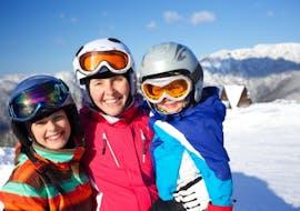 Een skileraar van Skischule Kahler glimlacht samen met twee kinderen tijdens de cursus Skilessen voor kinderen (6-15 jaar) - Middag - Gevorderden.