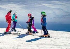 Des enfants écoutent les instructions de leur moniteur de ski pendant leur cours de ski pour enfants (6-12 ans) - expérimenté avec l'école de ski ESF Vallorcine.
