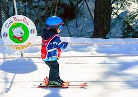 Un enfant est ammené au sommet de la montagne par les remontées mécaniques pour son cours particulier de ski enfants - vacances - tous niveaux avec l'école de ski ESF Vallorcine.