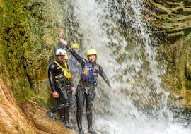 Three people are stood under a waterfall while canyoning in the Cetina River with Active 365.