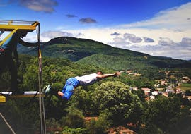 """A man is doing a jump during his Bungee Jumping """"Seajump"""" from Viaduc Boussagues (50m) activity with Elastic Natural Bungee."""