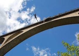 A man is bungee jumping from the 65m high Viaduc Pélussin supervised by an instructor of Elastic Crocodil Bungee.