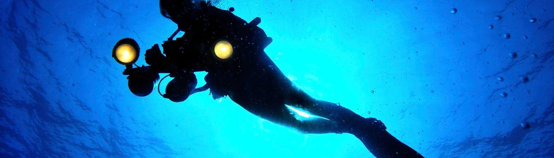 A tourist is swimming during his trial scuba diving for beginners in l'île rousse with EPIR Plongée.