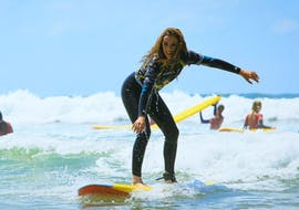 A surfer succeeds in surfing a wave thanks to her surfing lessons on the Côte des Basques Beach with La Vague basque.
