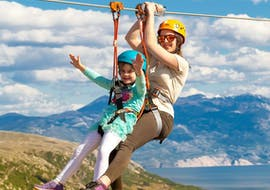 """An experienced guide from Edison Zipline Krk is gliding with a young girl on a zipline during the zipline tour """"Explore Krk"""" on the Island of Krk in Croatia."""