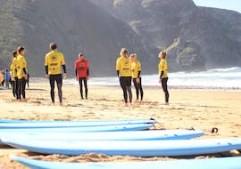 During the surfing lessons for kids & adults at Praia da Arrifana, a group of surfers is getting ready with a certified surf instructor from Arrifana Surf School.