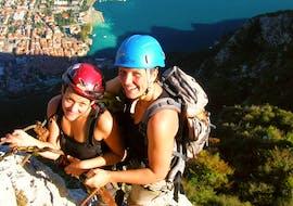 Eine junge Frau wagt sich während des Klettersteigs Via dell'Amicizia mit dem Guide von Skyclimber in luftige Höhen.