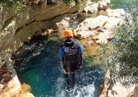 A participant of the River Trekking in Gorges du Loup for Young & Old tour with FunTrip is jumping into a beautiful pool of clear water.