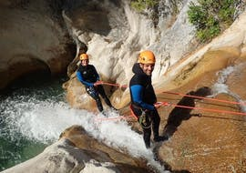 Two friends are abseiling down the canyon during their Canyoning in the Gours du Ray Canyon - Aquatic tour with FunTrip.