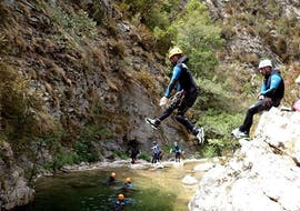 A participant of the Canyoning in Canyon de La Bollène - Day Discovery tour with FunTrip is jumping into the river.
