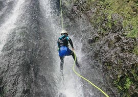 """During the Canyoning """"Intermediate"""" - Madeira with Epic Madeira, a participant is bravely roping down over a thunderous waterfall."""