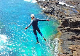 A participant of the Coasteering at Ponta de São Lourenço with Epic Madeira is jumping into the turquoise water of the ocean.