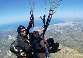 During the tandem paragliding above Chania, a man is taking a selfie with his certified tandem pilot from Cretan Paragliding.