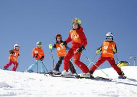 Four children smiling and skiing together with their instructor during their lessons kids ski lessons in Rohrmoos with Skischule Tritscher.