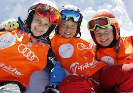 Three children are laying in the snow smiling during their kids ski lessons in Planai.
