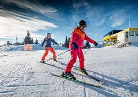 An instructor from skischule Tritscher is teacher a woman how to ski plough during Adult Ski Lessons for First Timers in Planai.