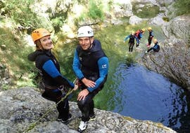 Two friends are getting ready to do an abseiling descent during their Canyoning in Gorges du Loup - Level 2 tour with FunTrip.