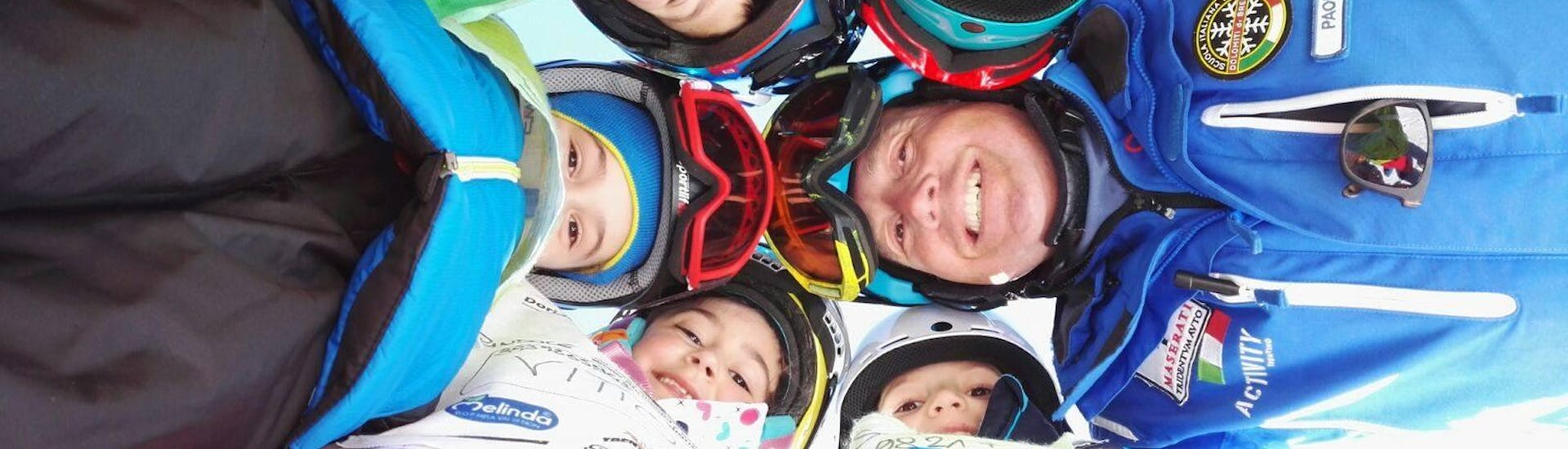 Kids and ski instructor taking a picture in Andalo during one of the Kids Ski Lessons (6-14 y.) for Advanced Skiers.