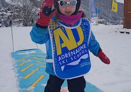 A little girl has fun during her kids ski lessons children from 3 to 5 years 6 Max with Adrenaline Verbier.