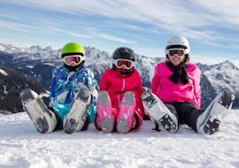 3 enfants profitent de leur pause pendant des cours de ski pour enfants débutants avec l'école de ski SMT Mayrhofen au Tyrol.