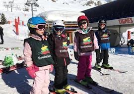 """Quatre jeunes skieurs apprennent à skier dans l'environnement sûr du Kids Club de l'école de ski Evolution 2 Tignes pendant leur Cours de ski pour Enfants """"Kids Club"""" (3-5 ans) - Matin."""