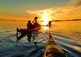 """Participants of the Sea Kayak Tour """"Sunset"""" in Lofoten organized by Northern Explorer are paddling in the sunset light"""