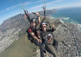 Happy woman flys with her tandem pilot over the sea, enjoying the beatiful view during paragliding in cape town with Hi5 Tandem Paragliding Cape Town.