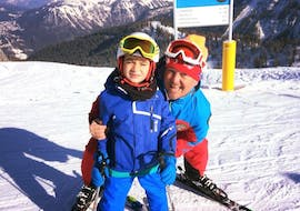 A kid is smiling at the camera with his ski instructor during the Kids Ski Lessons (3-5 y.) - First Timer organized by the ski school Scuola di Sci Val Rendena in the ski resort of Pinzolo.