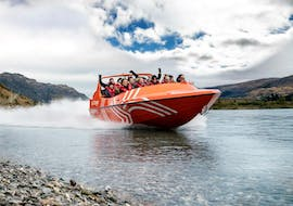 Participants of the Jet Boat Tour from Queenstown are enjoying the ride on the shoreline of Lake Wakatipo with the guides from Go Orange