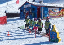 A group of 5 skiers is learning how to ski at the Kinderland with Top Secret ski and snwoboard school in Davos.