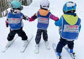 3 little skiers are participating in kids ski lessons for advanced skiers with Top Secret ski and snowboard school in Davos.