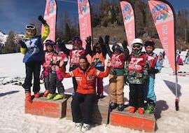 The Kids Ski Lessons (5-12 y.) - Advanced is over and the participants in the final race are on the podium, the ski school Scuola Italiana di Sci Civetta teacher celebrates with them.