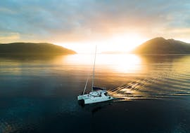 Our beautiful catamaran bathing in the midnight sunlight during the Arctic Midnight Sunset Boat Tour in Tromsø with Pukka Travels.