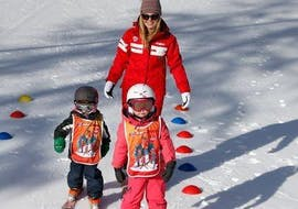 """Deux kids are learning how to stand on their skis during their Kids Ski Lessons """"Piou-Piou"""" (3-5 years) with the ski school ESF du Dévoluy."""