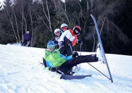 A ski instructor is posing on the slope with some young skiers during the Kids Ski Lessons (4-14 y.) - All Levels organized by Maestri di Sci Cristallo - Monte Bondone in the ski resort of Monte Bondone.