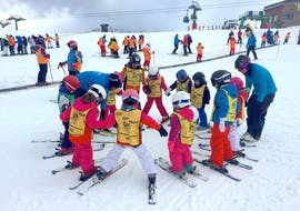Children warm up with their ski instructor and form a circle during the kids ski lessons (6-14 years) - Puente inmaculada + Christmas with the ski school Escuela Española de Esquí Panticosa.