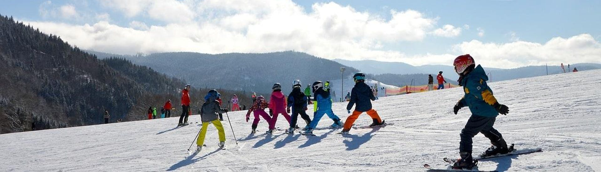 Kids are skiing down a slope during their Kids Ski Lessons (5-12 years) - Experienced with the ski school Moonshot La Bresse.