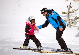 A young skier is learning to ski a private ski instructor during a Private Ski Lessons for Kids - Beginner organized by the ski school Scuola di Sci Tre Nevi Ovindoli in the ski resort of Ovindoli on the Monte Magnola.