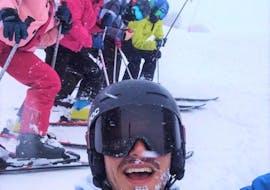 A group of participants of a ski lesson is smiling at the camera with the private ski instructor during the Private Ski Lessons for Kids - With Experience organized by the ski school Scuola di Sci Tre Nevi Ovindoli in the ski resort of Ovindoli.