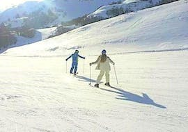 A private ski instructor is mastering the slope with a participant during the Private Ski Lessons for Adults - With Experience organized by the ski school Scuola di Sci Tre Nevi Ovindoli in the ski resort of Ovindoli on the Monte Magnola.