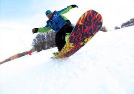 A private snowboard instructor is mastering the board during the Private Snowboarding Lessons for Kids & Adults organized by the ski school Scuola di Sci Tre Nevi Ovindoli in the ski resort of Ovindoli on the Monte Magnola.