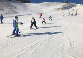 A group of young skiers is learning how to ski during one of the Kids Ski Lessons (4-14 y.) - Beginner organized by the ski school Scuola di Sci Tre Nevi Ovindoli in the ski resort of Ovindoli on the Monte Magnola.