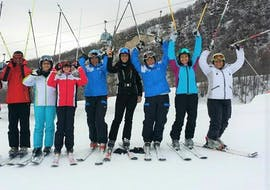A group of skiers is posing at the camera during the Ski Lessons for Adults - With Experience organized by the ski school Scuola di Sci Tre Nevi Ovindoli in the ski resort of Ovindoli on the Monte Magnola.
