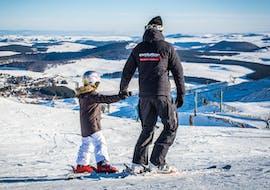 Un moniteur de ski de l'école de ski Evolution 2 Super Besse tient la main d'un enfant en haut des pistes avant de commencer leur Cours particulier de ski pour Enfants - Tous âges.