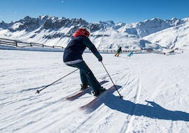 A skier is skiing down a snowy slope with confidence during their Private Ski Lessons for Adults - Praz sur Arly & Flumet with the ski school ESI Snow Diam's.