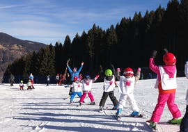 A ski instructor is teaching a group of young skier how to ski safetly on the slopes during the Kids Ski Lessons (5-14 years) - Weekend - All Levels organized by the ski school Scuola di Sci Pinzolo in the Val Rendena ski resort.